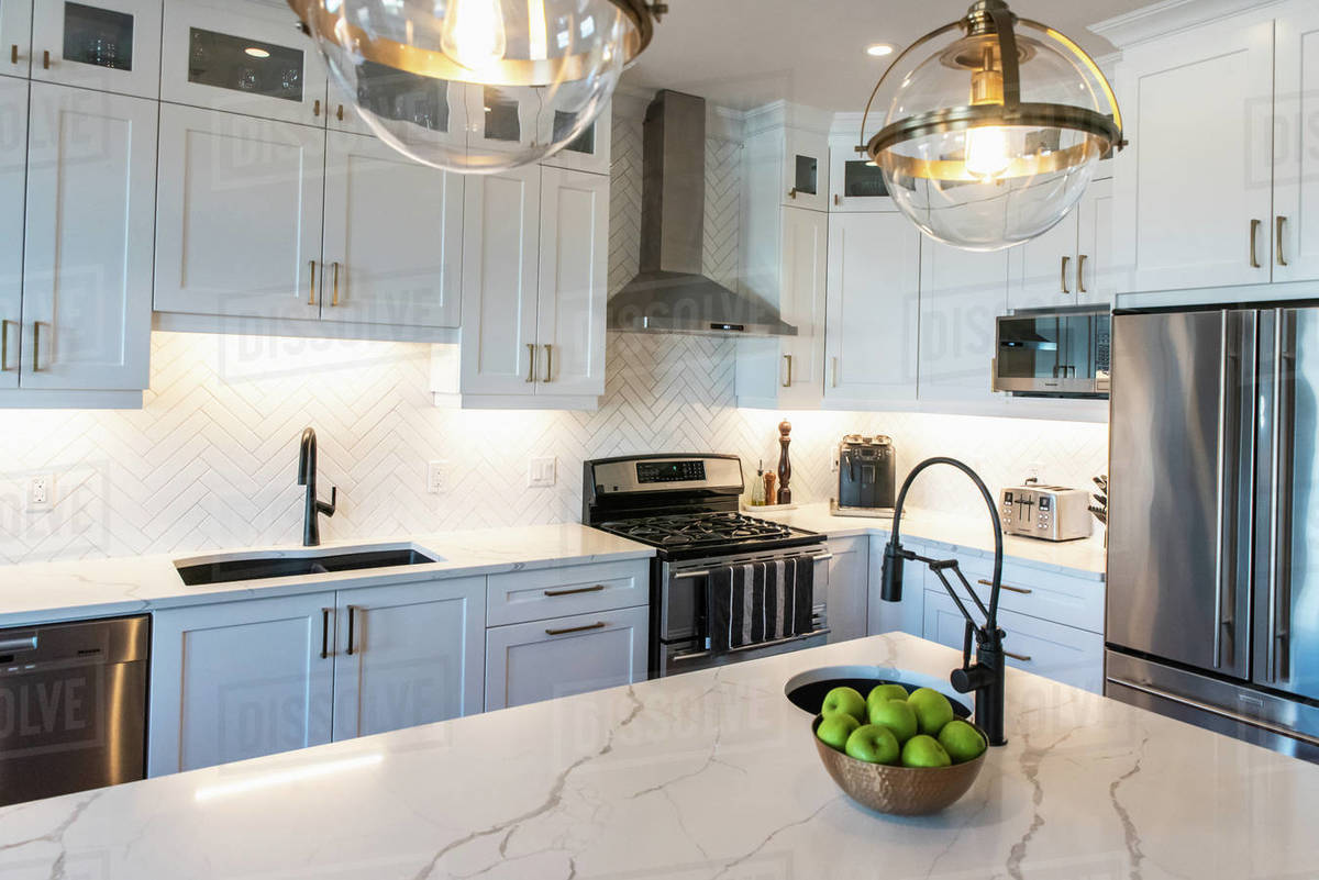 Modern kitchen with white cupboards, dark island and gold accents. Royalty-free stock photo