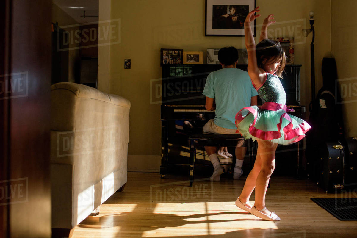 A little girl in tutu raises her arm to dance to father's piano music Royalty-free stock photo