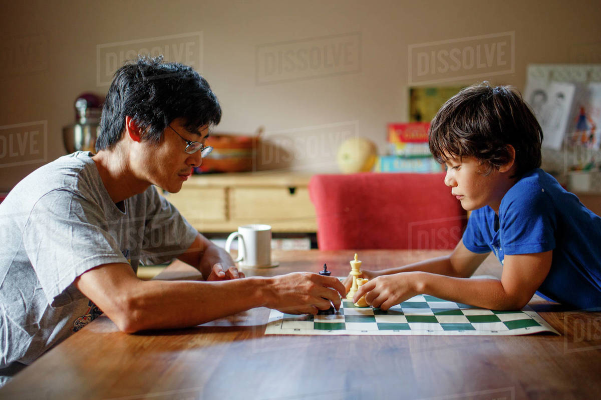 A father and son sit together at a table playing a game of chess Royalty-free stock photo