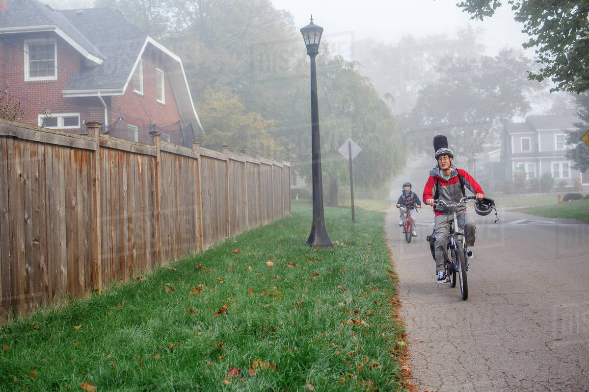 A father and son bike together on a foggy tree-lined street Royalty-free stock photo