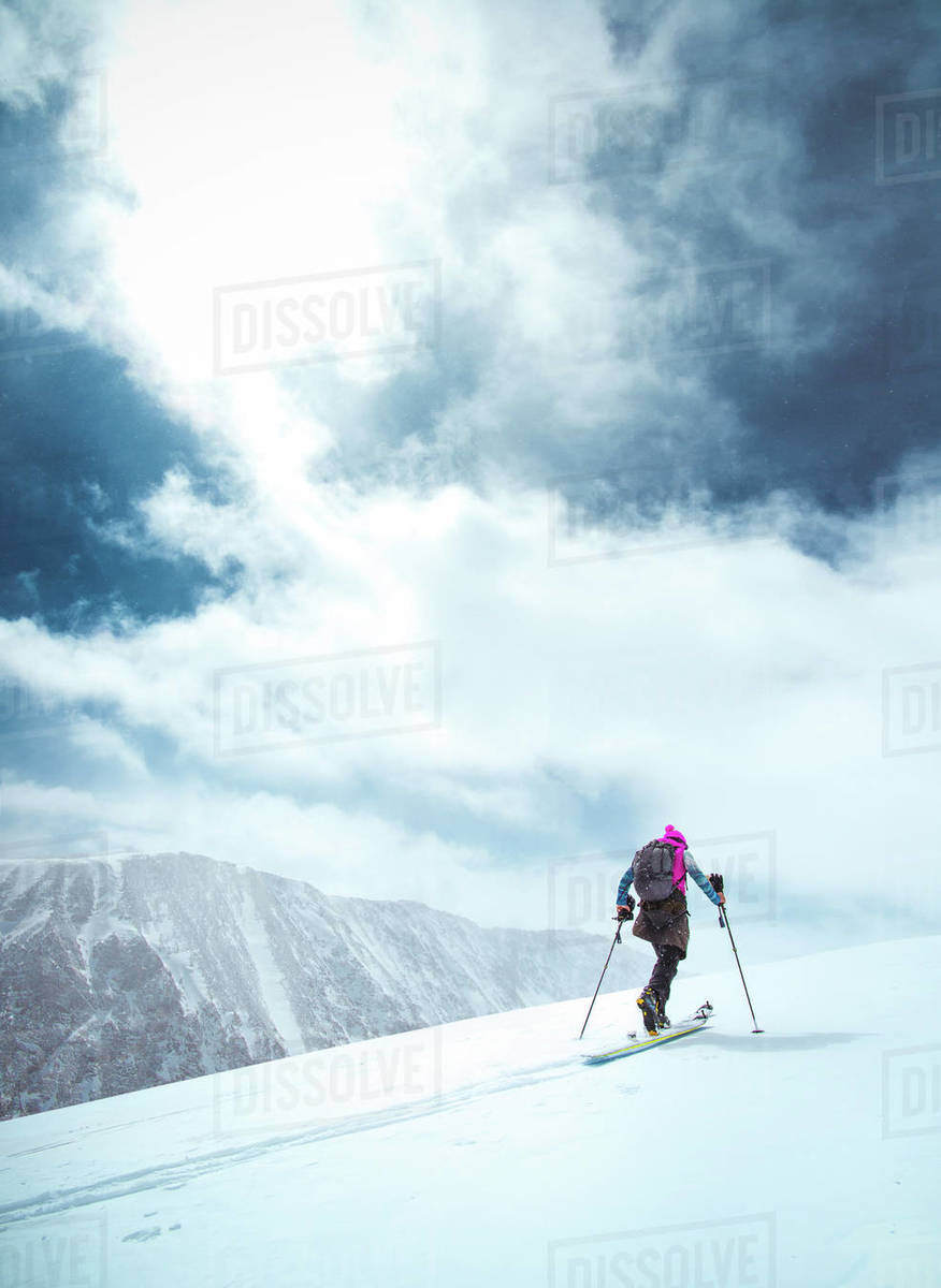 A skier tours up a snowy mountain in Colorado with blue skies Royalty-free stock photo