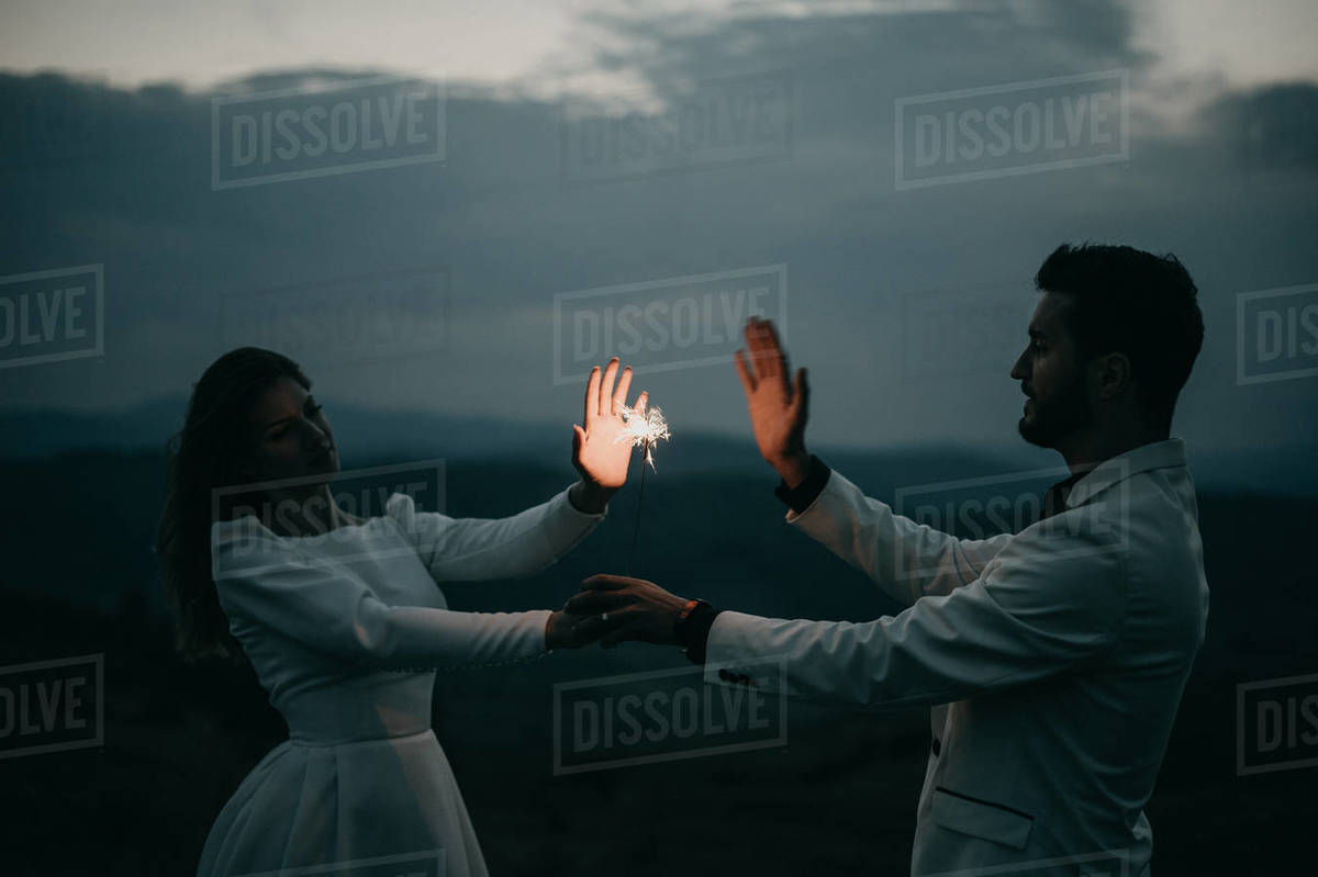 Happy Young Couple Playing with a firework at night After Wedding Royalty-free stock photo