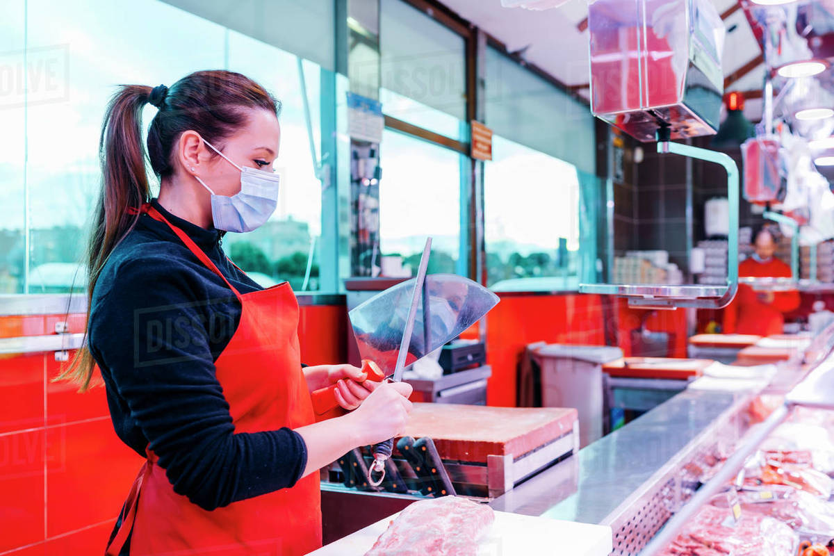 Butcher woman sharpening the knife to cut meat Royalty-free stock photo