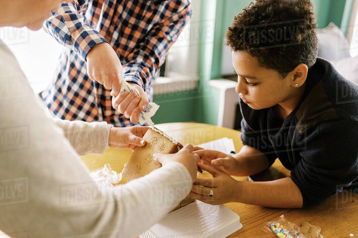 A family making a gingerbread house together in the living room Royalty-free stock photo