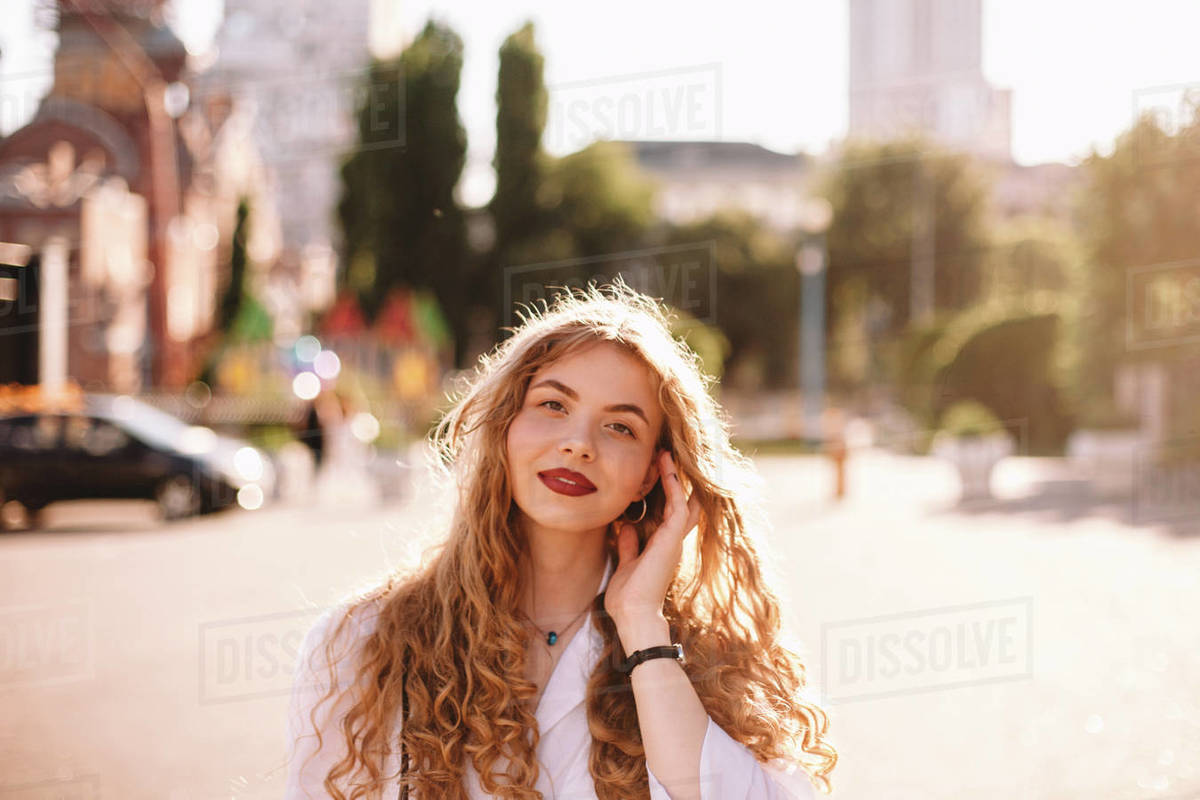 Portrait of tired young woman standing in city during summer Royalty-free stock photo