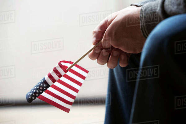 Cropped image of person holding American flag Royalty-free stock photo