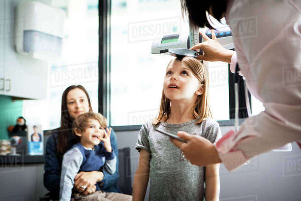Doctor measuring girl's height while family sitting at clinic Royalty-free stock photo