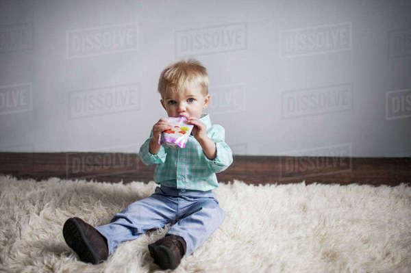 Portrait of cute baby boy drinking juice from package while sitting on rug at home Royalty-free stock photo