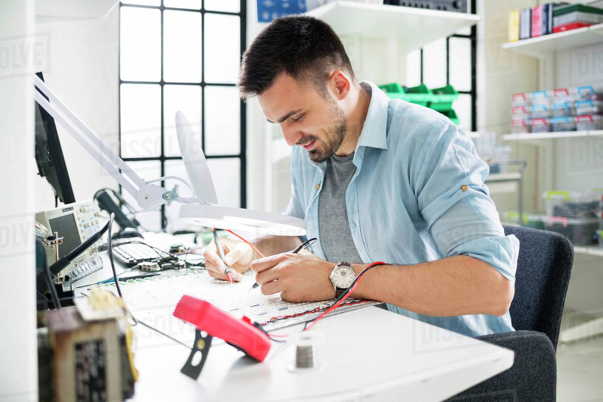 Smiling Technician Soldering Circuit Board At Table In Electronics Circuitboardtablejpg Laboratory