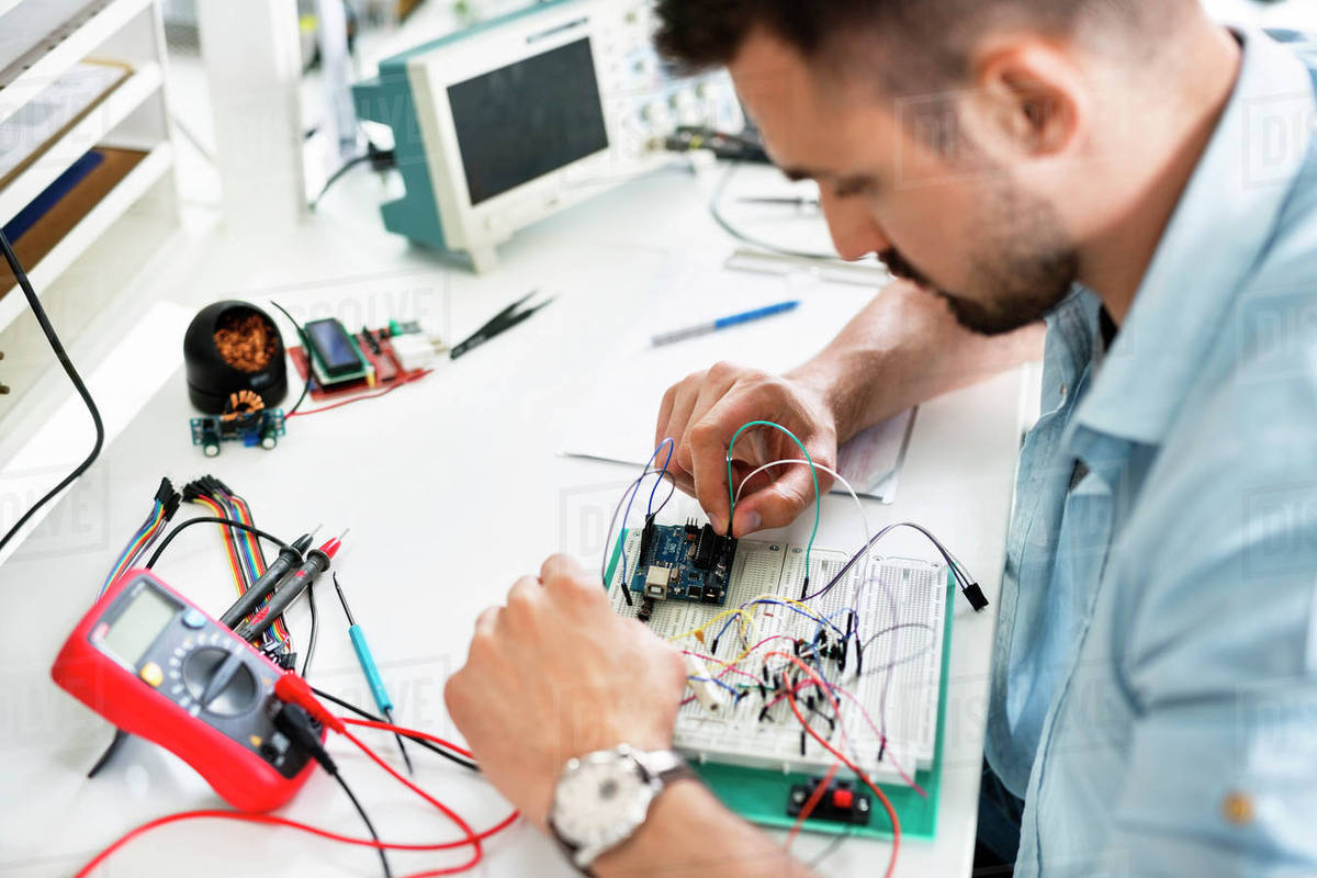 High Angle View Of Technician Analyzing Circuit Board At Table Circuitboardtablejpg