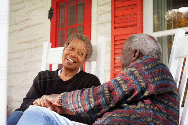 Senior couple sitting on porch and talking Royalty-free stock photo