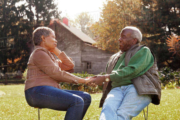 Senior couple sitting in garden, looking at each other, holding hands and smiling Royalty-free stock photo