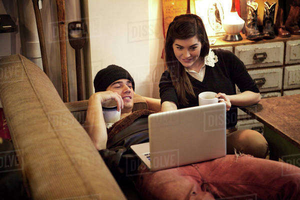 Boyfriend and girlfriend (16-17) in living room holding mugs and looking at laptop screen Royalty-free stock photo