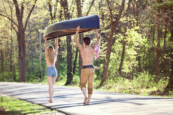 Couple walking on road in forest and carrying kayak Royalty-free stock photo