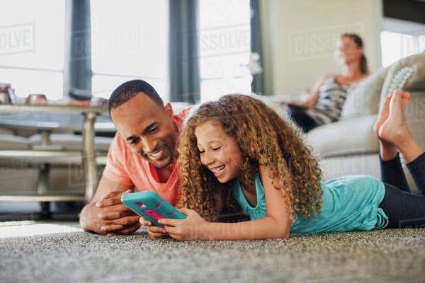 Happy father and daughter playing handheld game while lying on floor at home Royalty-free stock photo