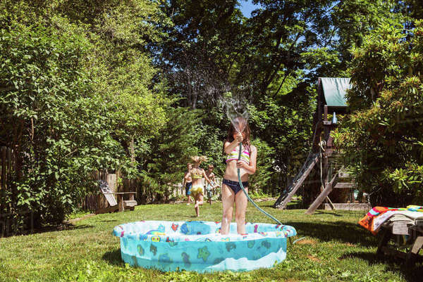Girl playing with water while standing in wading pool at yard Royalty-free stock photo