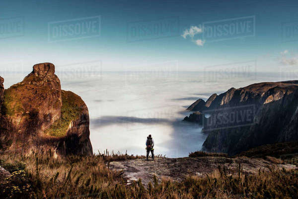Rear view of male hiker standing on mountain against sky Royalty-free stock photo