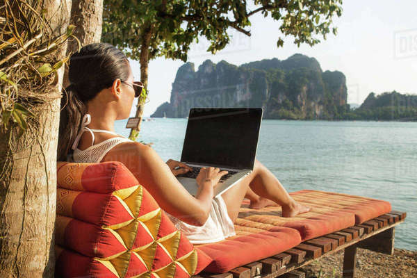 Woman using laptop computer while sitting on lounge chair against sea Royalty-free stock photo