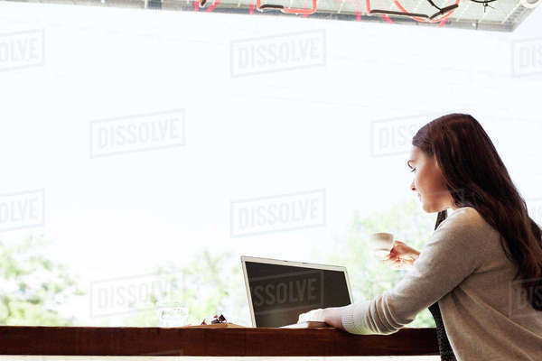 Low angle view of woman drinking coffee and using laptop computer at cafe Royalty-free stock photo