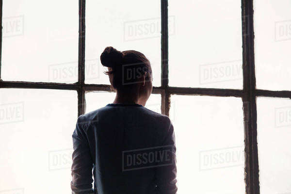 Young woman looking through window Royalty-free stock photo