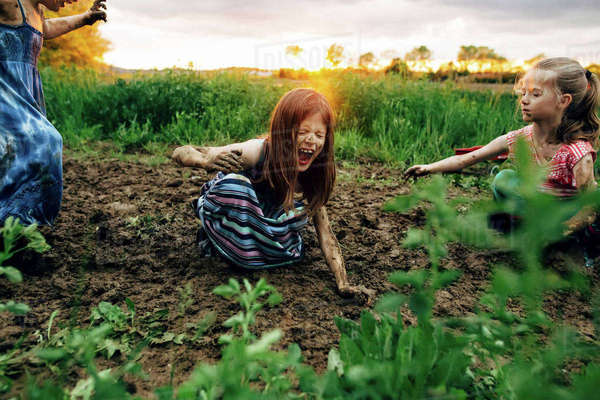 Girl with sisters shouting while crouching in mud Royalty-free stock photo