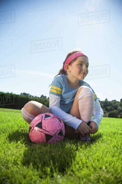 Girl tying shoelace while sitting with ball on grassy field Royalty-free stock photo