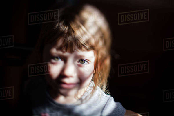 Close-up portrait of cute girl standing in dark room on sunny day Royalty-free stock photo