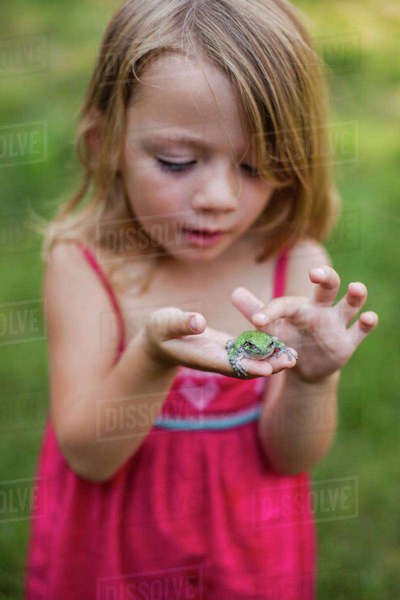 Cute girl playing with frog in yard Royalty-free stock photo