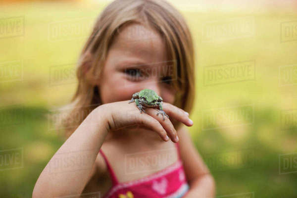 Portrait of playful girl with frog standing in yard Royalty-free stock photo