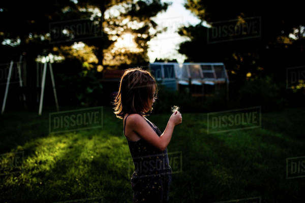 Side view of girl holding dandelion seed while standing at yard Royalty-free stock photo