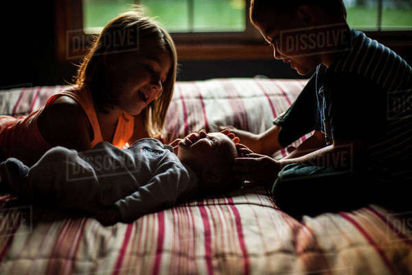 Siblings playing with baby girl on bed at home Royalty-free stock photo