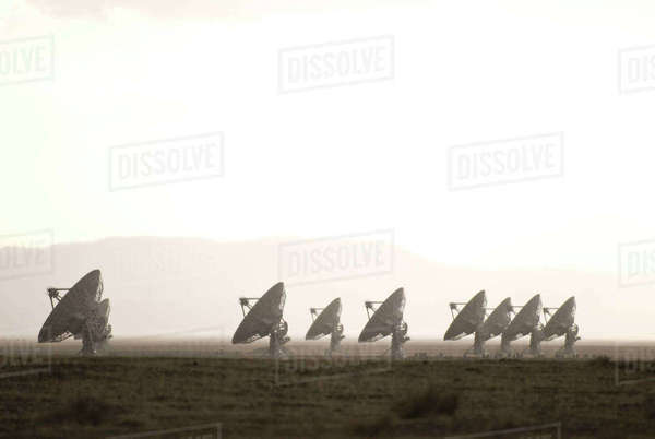 Satellite dish on field against sky during foggy weather Royalty-free stock photo