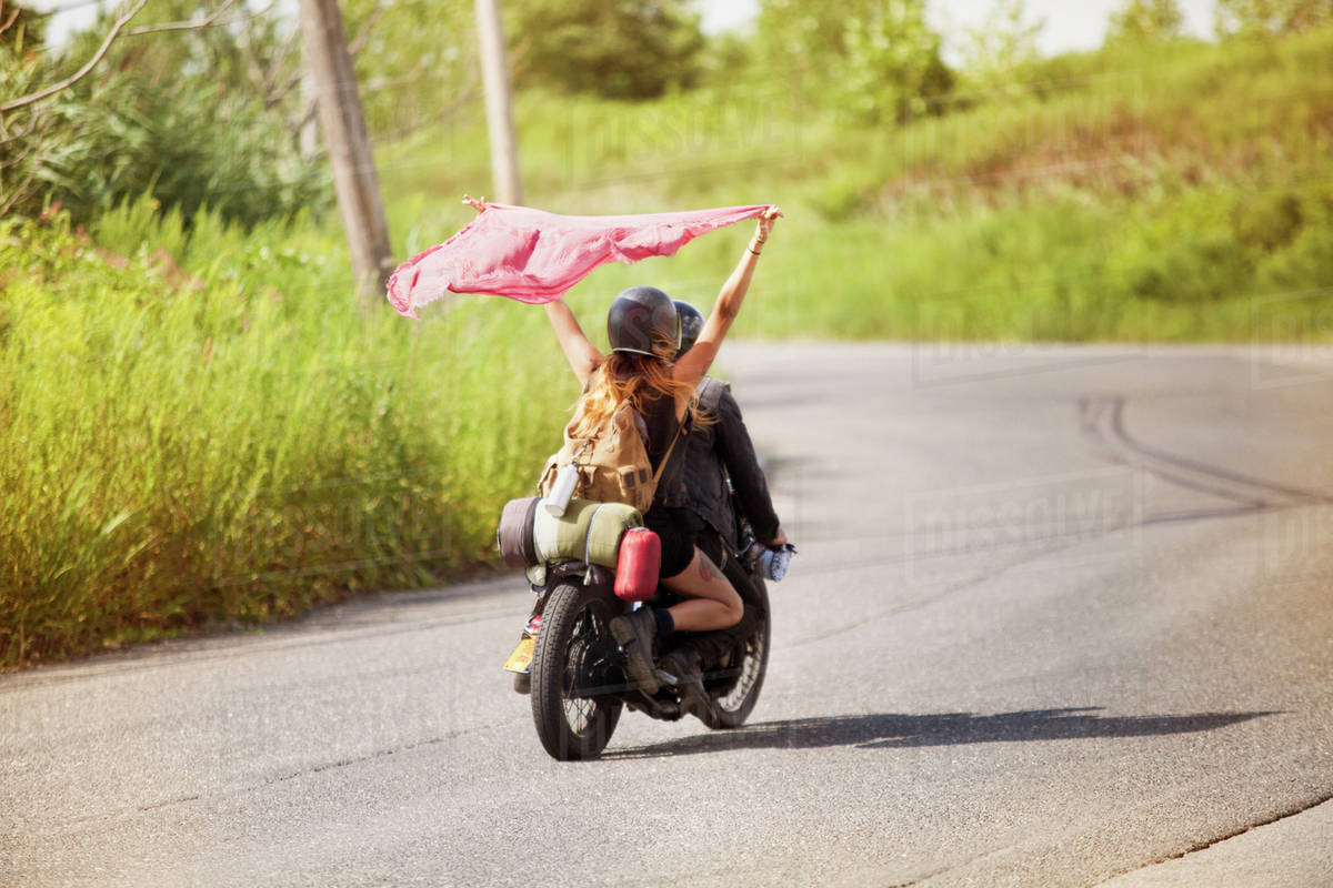 young couple riding motorcycle stock photo dissolve