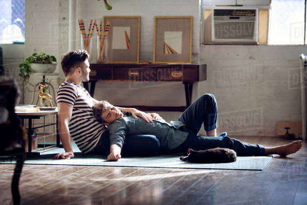 Homosexual couple relaxing on floor in living room Royalty-free stock photo
