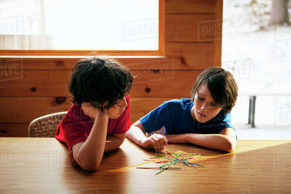 Brothers (8-9,  10-11) playing pick up sticks Royalty-free stock photo