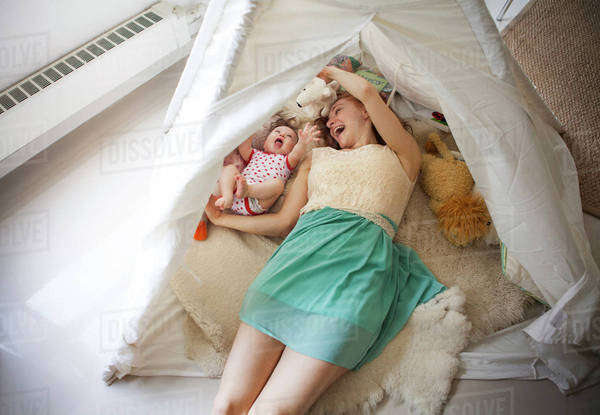 Mother playing with baby girl (6-11 months) in tent Royalty-free stock photo