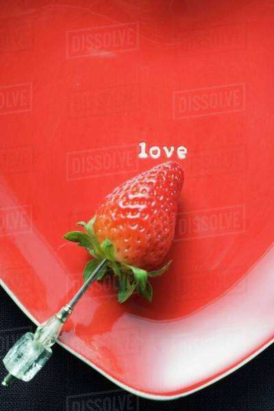 Strawberry on skewer on red heart-shaped plate Royalty-free stock photo