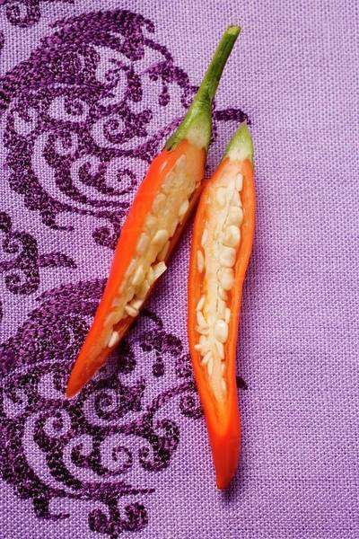 Red chili pepper, halved, on purple fabric Royalty-free stock photo