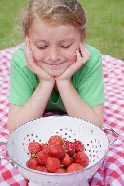 Girl looking at strawberries in colander Royalty-free stock photo