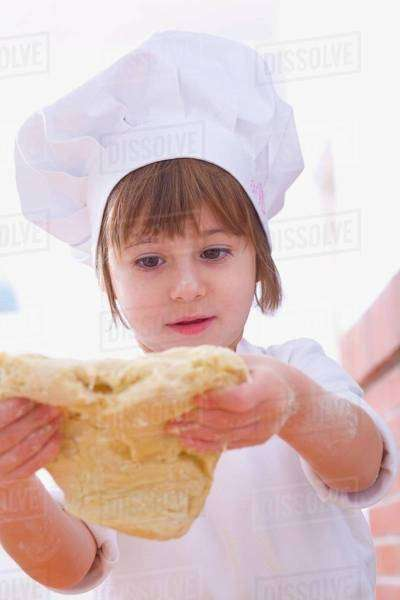 Girl in chef's hat handling pastry Royalty-free stock photo