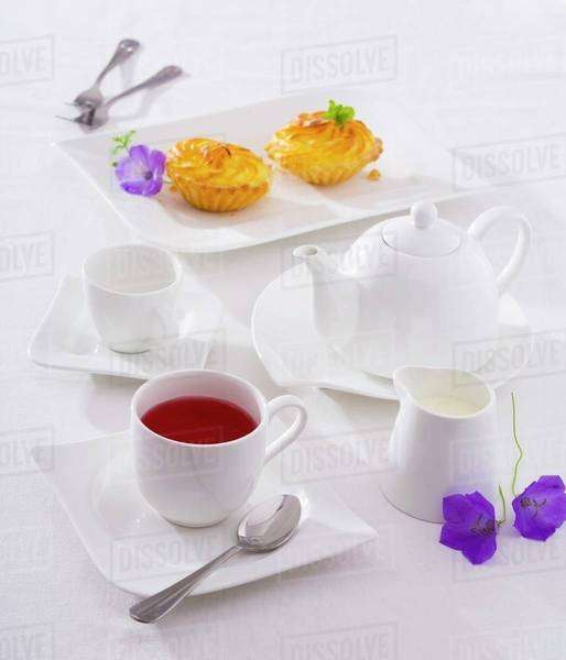 A cup of fruit tea, tea things and small cakes Royalty-free stock photo