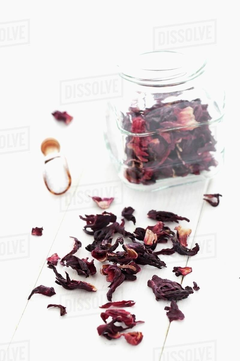 Dried hibiscus flowers in a jar and on a white cloth stock photo dried hibiscus flowers in a jar and on a white cloth izmirmasajfo