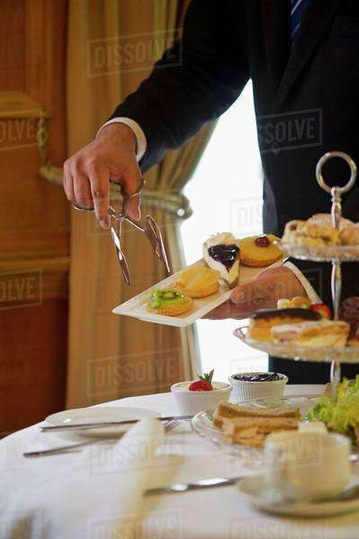 A waiter serving cakes with afternoon tea (England) Royalty-free stock photo