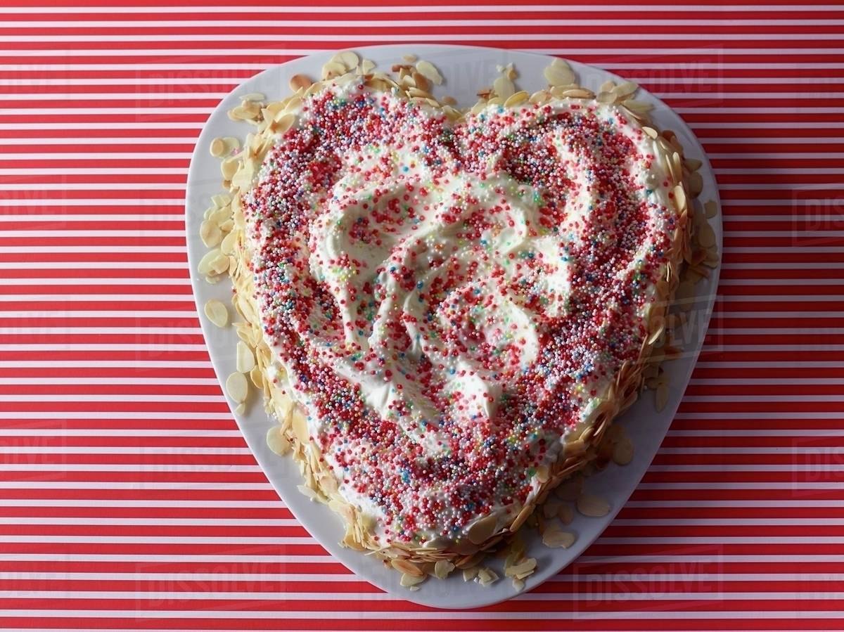 A heart-shaped cake decorated with colourful sprinkles and flaked almonds  stock photo