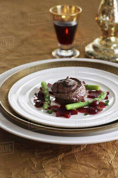 Beef roulade with beetroot stars and green asparagus Royalty-free stock photo