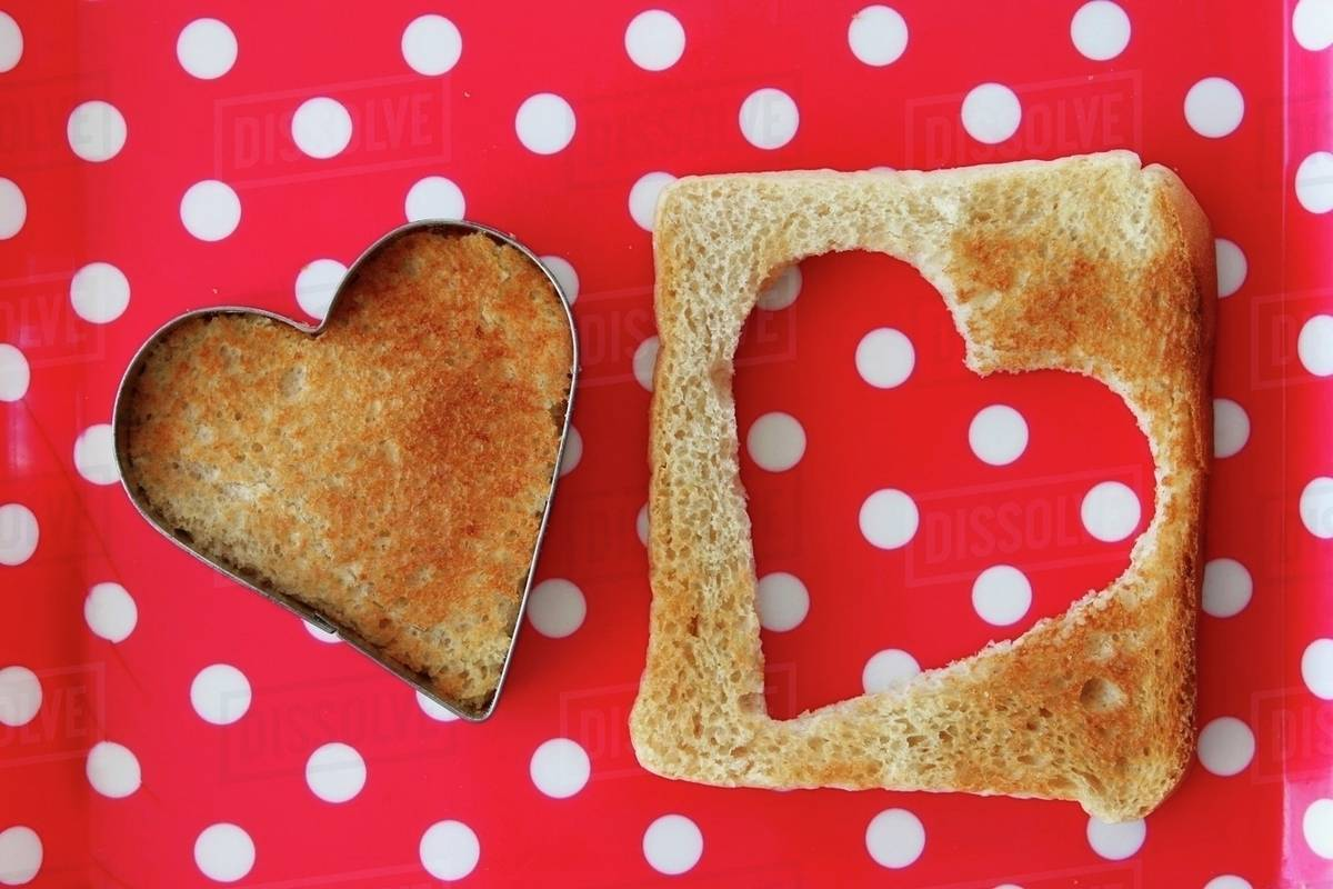 a heart cut out of a slice of toast stock photo dissolve