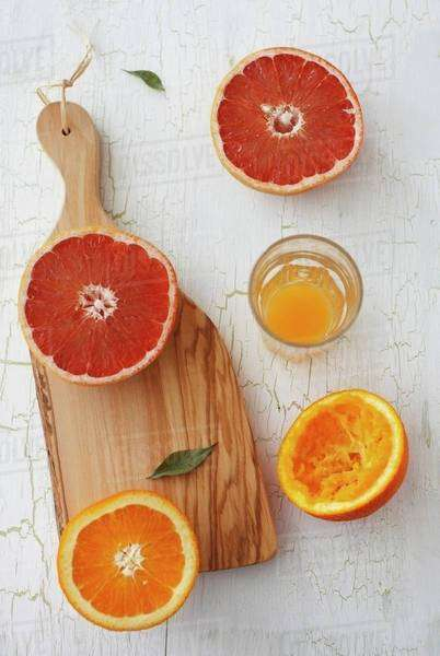 An orange and a grapefruit, cut in half, with orange juice squeezed from one orange half Royalty-free stock photo