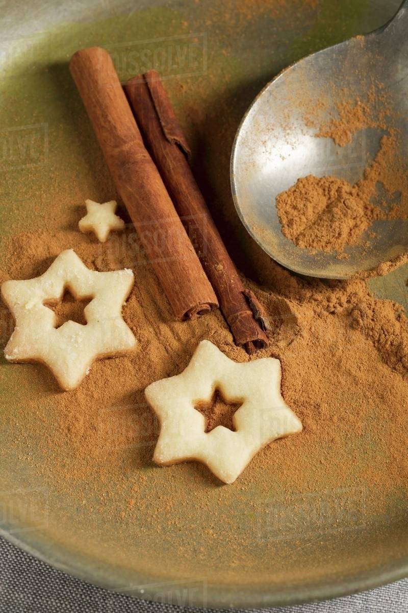 Star Shaped Biscuits Ground Cinnamon Cinnamon Sticks And A Spoon Stock Photo
