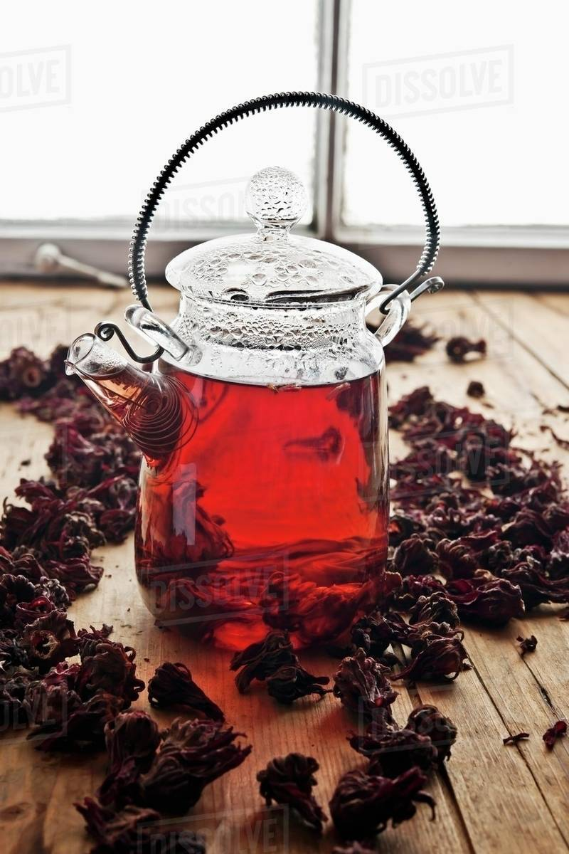 Hibiscus tea in a glass teapot surrounded by hibiscus flowers hibiscus tea in a glass teapot surrounded by hibiscus flowers izmirmasajfo