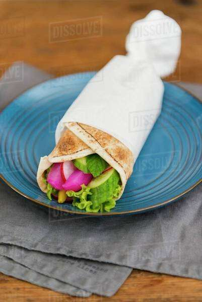 Vegetarian wrap with cucumber, salad leaves, peppermint, pickled radish and fresh radish Royalty-free stock photo